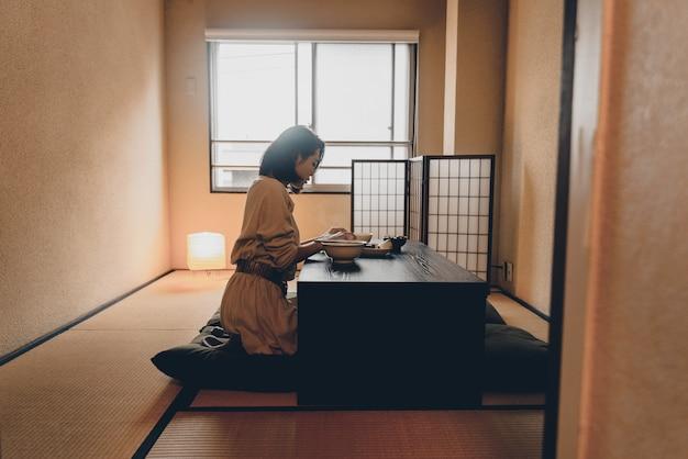 伝統的なアパートで食べる日本人女性