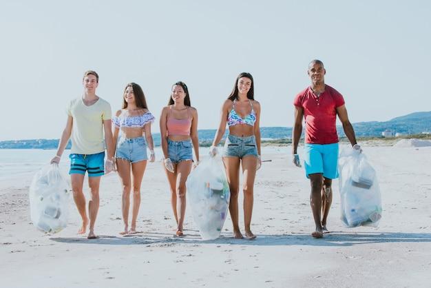 Группа активистов друзей собирает пластиковые отходы на пляже. люди убирают пляж, с сумками. понятие об охране окружающей среды и проблемах загрязнения океана