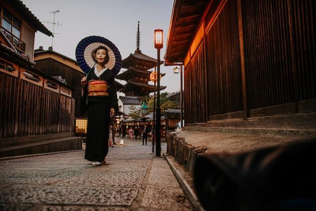 Красивая японская старшая женщина гуляя в село. типичный японский традиционный образ жизни