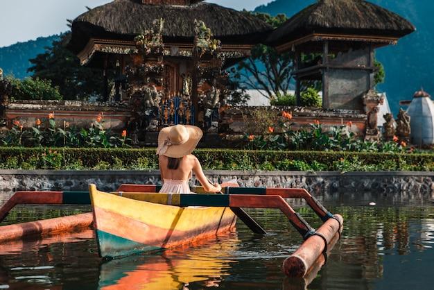 Путешественник молодой женщины на деревянной лодке на пура улун дану братан