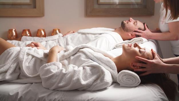 豪華なスパでヘッドマッサージを楽しんでいるマッサージベッドに横たわっている美しいカップル。