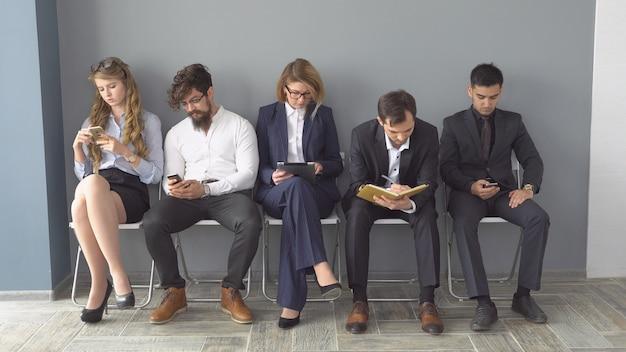 Безработных ожидают собеседования, сидящие на стульях в коридоре офисного здания.