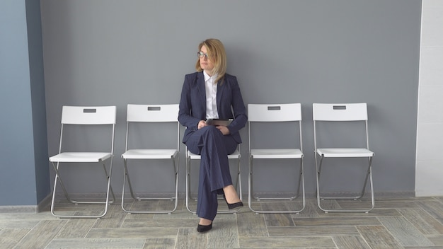 Уверенно бизнес женщина держит в руках планшетный компьютер. привлекательная женщина в деловой одежде в офисе. портрет предпринимателей.