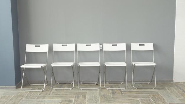 Молодые люди ожидают интервью, сидя на стульях в офисном здании. собеседование для работы. новобранцы скучают и наслаждаются гаджетами.
