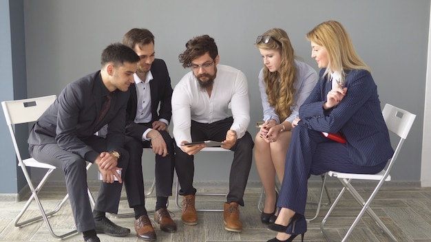 Деловая встреча в неформальной обстановке. молодой предприниматель показывает информацию коллегам на экране планшетного пк.