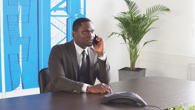 若い黒人実業家がオフィスで電話を使用して