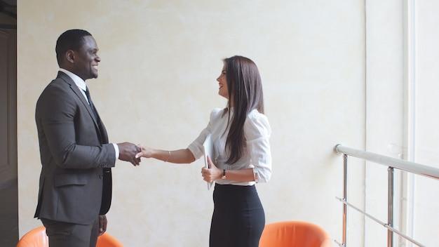 会議で握手するビジネス人々