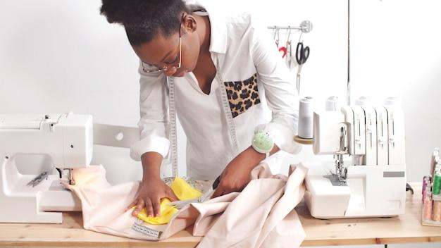 アフリカ系アメリカ人の軽装の仕立て屋がミシンで服を縫う