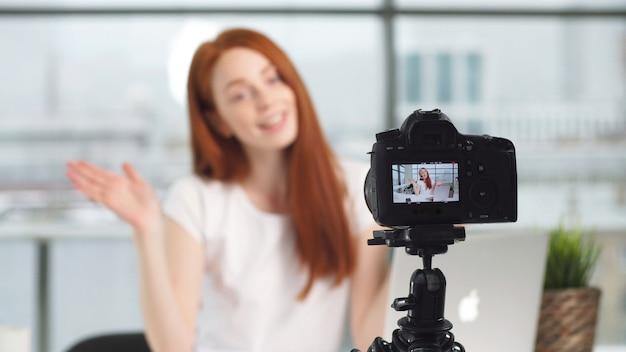 カメラで撮影しながらオフィスで働く若い美しいブロガーの女の子