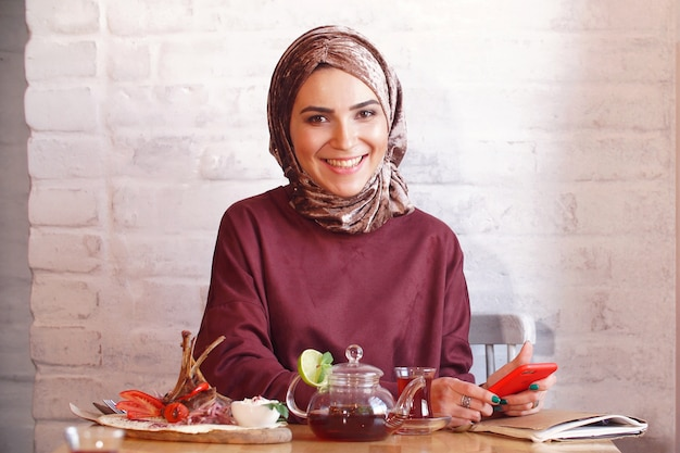 若いイスラム教徒の女性は彼女の手でスマートフォンを保持し、カメラの笑顔のポーズ