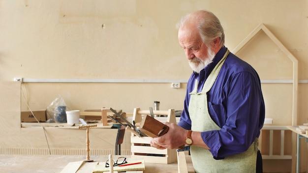 Плотник с седыми волосами работает в своей мастерской. концепция деревообработки