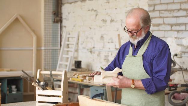 Бородатый плотник с седыми волосами работает с деревянными заготовками