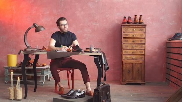 Дизайнер обуви рисует что-то в мастерской по ремонту обуви