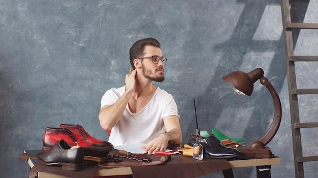 Серьезный сапожник в очках делает набросок для ремонта обуви