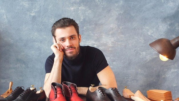 Молодой дизайнер обуви смотрит в камеру показывает свою работу