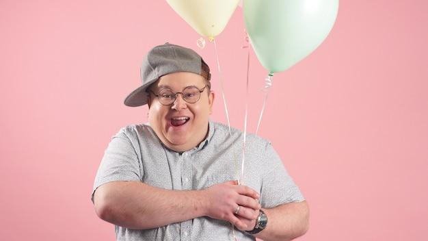 分離されたピンクの背景に、風船でくまのプーさんに非常によく似た陽気な面白い男がスタジオでしかめっ面