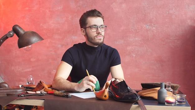 Серьезный сапожник, в процессе изготовления обуви