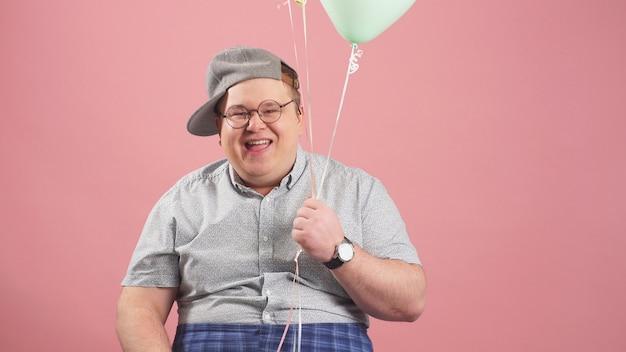 ピンクの背景に分離された風船でくまのプーさんに非常に似ている陽気な肉付きの良い男がスタジオでしかめっ面