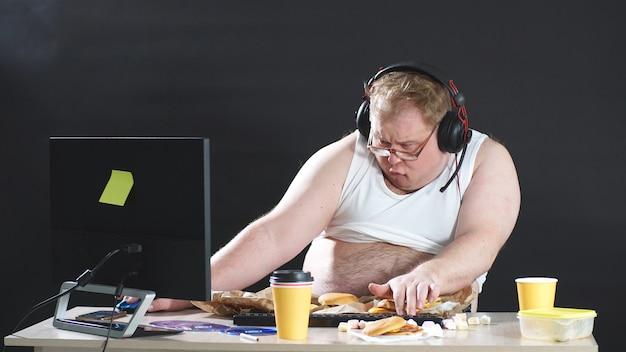 Ленивый, пухлый мужчина в футболке и наушниках бродит по сети. людям нравятся компьютерные игры. концепция наркомании