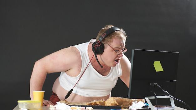 Кричащий человек во время игры в видеоигры на компьютере, человек получает как можно больше удовольствия в карантине, самоизоляции