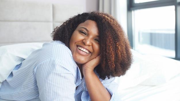 Портрет пухлой жизнерадостной девушки в пижаме, сидящей на кровати и смотрящей в камеру