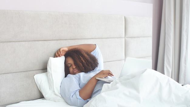 Молодая афроамериканка уснула дома в постели, работая удаленно на ноутбуке. самоизоляция, удаленная работа
