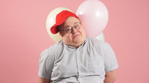 ピンクの背景に風船を保持している赤い野球帽の陽気なデブ男
