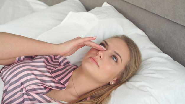 Симпатичная блондинка с голубыми глазами просыпается утром в постели