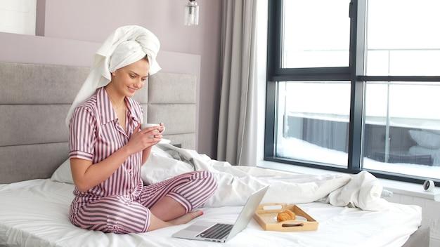 Привлекательная девушка, сидя на кровати, работает на ноутбуке. самоизоляция, карантин, коронавирус