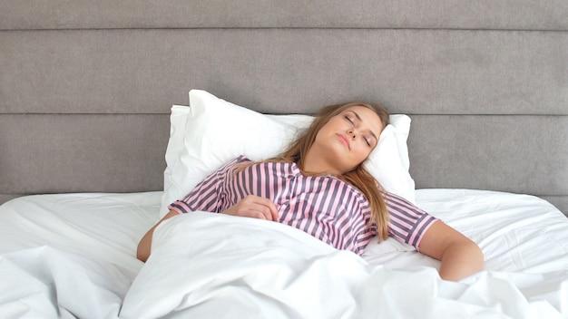 Милая девушка спит в удобной кровати. много свободного времени на карантине