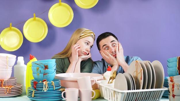 結婚されていたカップルは、孤立した背景のテーブルに立っている汚れた皿の量が怖い