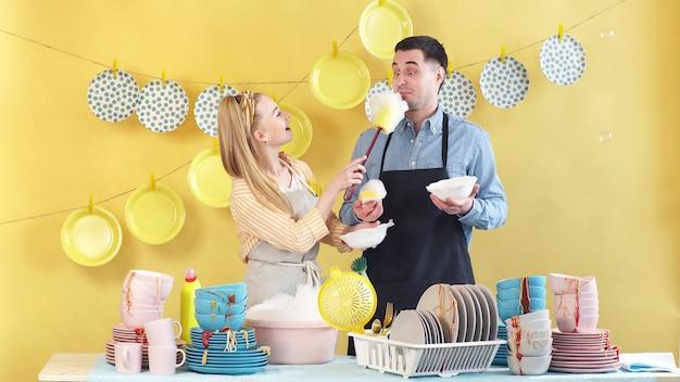 若いカップルがパーティー、孤立した背景の後汚れた皿の山の近くに立つ