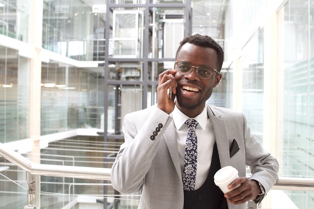 手に一杯のコーヒーを保持しているスマートフォンで話している黒のスーツのビジネスマンを笑顔