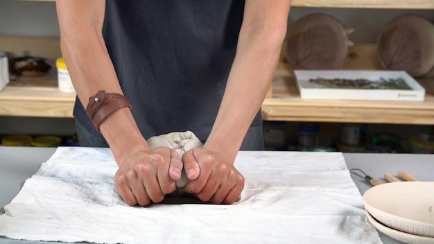女性の手は粘土をこねて陶器を作ります。