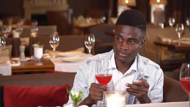 Черный человек пьет красное вино в ресторане.