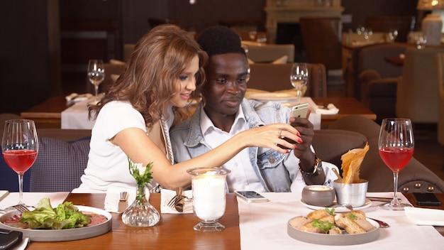Молодая пара в ресторане с помощью смартфона.