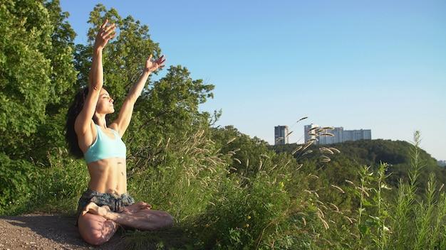 Красивая молодая женщина практикует движения йоги и позиции на открытом воздухе на невероятной скале.