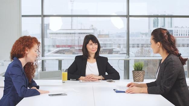 木製の会議テーブルでビジネスドキュメントを積極的に勉強するビジネス女性パートナー