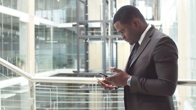 アフリカ系アメリカ人のビジネスマンが彼のスマートフォンでメールを読んでテキストメッセージの回答