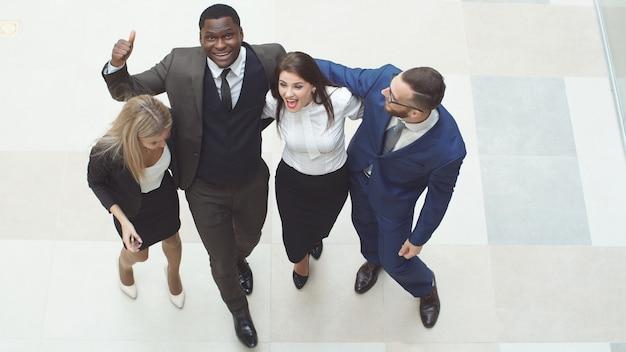 一緒に立っている幸せで多様なビジネス人々のグループの肖像画。彼らは空中ジャンプし、ビジネスの成功を祝うために応援します。
