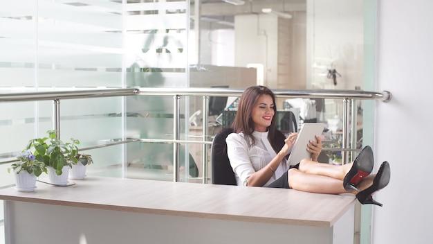 ビジネスの女性は、職場でタブレットコンピューターを使用します。