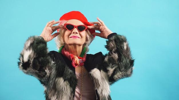 Портрет жизнерадостной пожилой женщины в солнечных очках