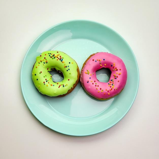 Две вкусные пончики разных цветов на синюю тарелку