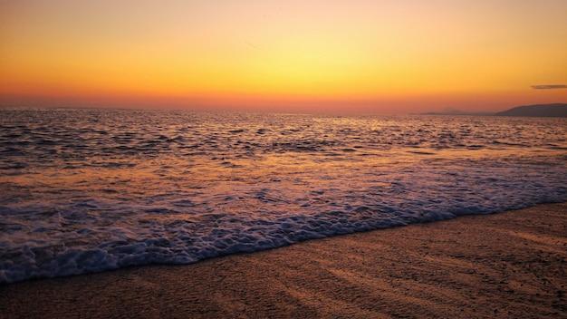 Сочетание заката и пляжа. красочный оранжевый закат на пляже