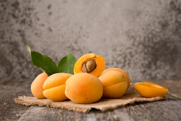 Свежие органические абрикосы с листьями на деревянном пространстве