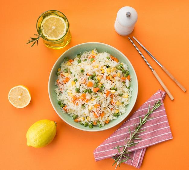Тарелка белого риса с овощами на стильной трендовой оранжевой стене, азиатская еда, вид сверху