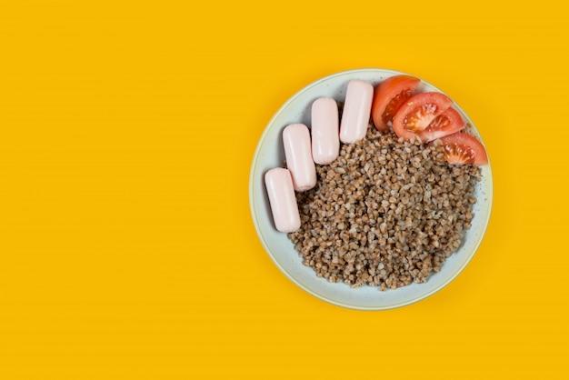 調理されたそば、ソーセージ、黄色のトレンドの背景にトマトのプレート