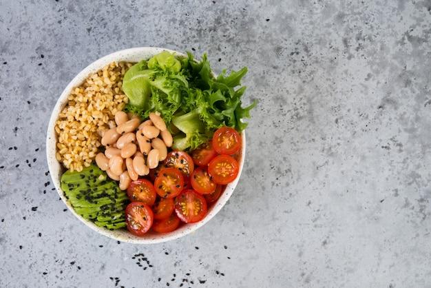 Тарелка свежего салата с белой фасолью, булгуром, помидорами черри и авокадо, украшенная черным кунжутом. горизонтальное фото с копией пространства, вид сверху