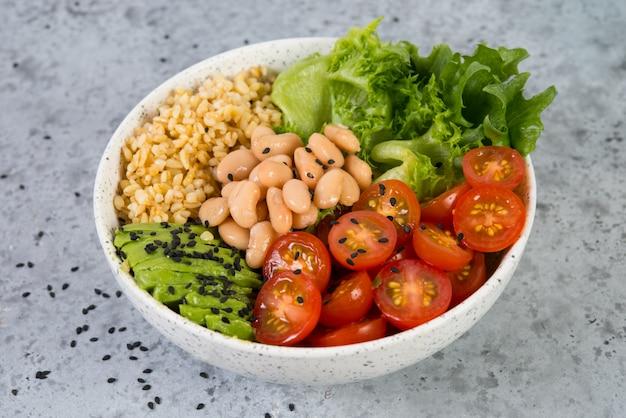 Тарелка свежего салата с белой фасолью, булгуром, помидорами черри и авокадо, украшенная черным кунжутом. горизонтальное фото