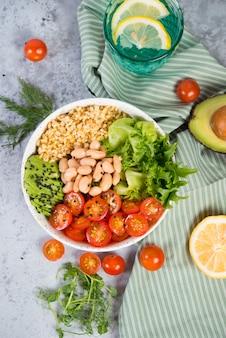Тарелка свежего салата с белой фасолью, булгуром, помидорами черри и авокадо, украшенная семенами черного кунжута с продуктами вокруг тарелки. вертикальное фото, вид сверху